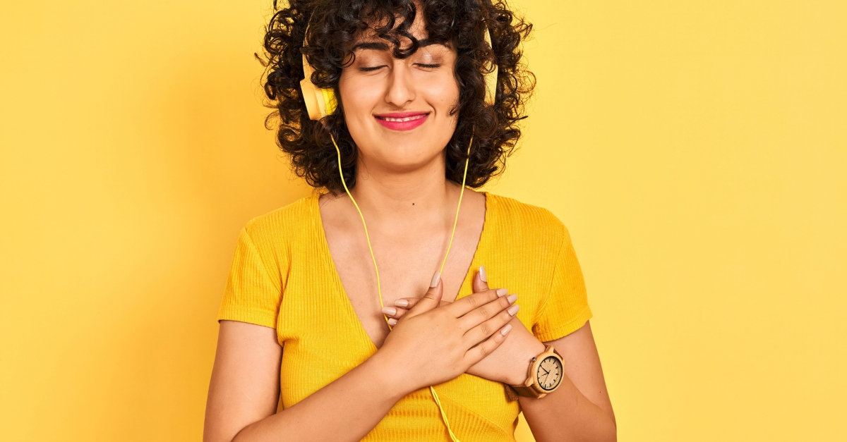 woman on yellow background listening to worship music with headphones hand over heart