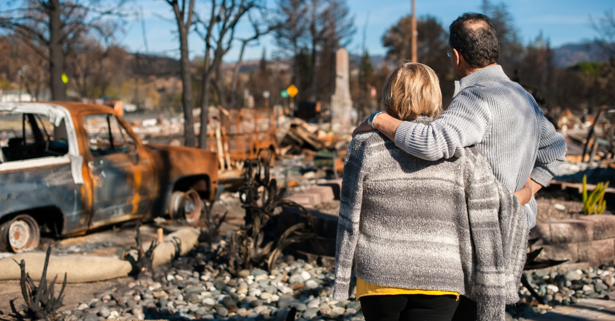 adult couple standing looking at burned house, prayer for california fires