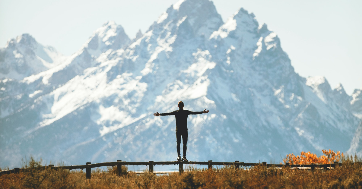 Person standing on a fence in front of a mountain praising the Lord, Study finds that there is a correlation between pattern recognition and belief in God