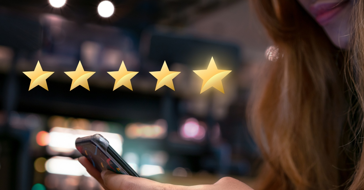 woman on smartphone pressing five gold stars