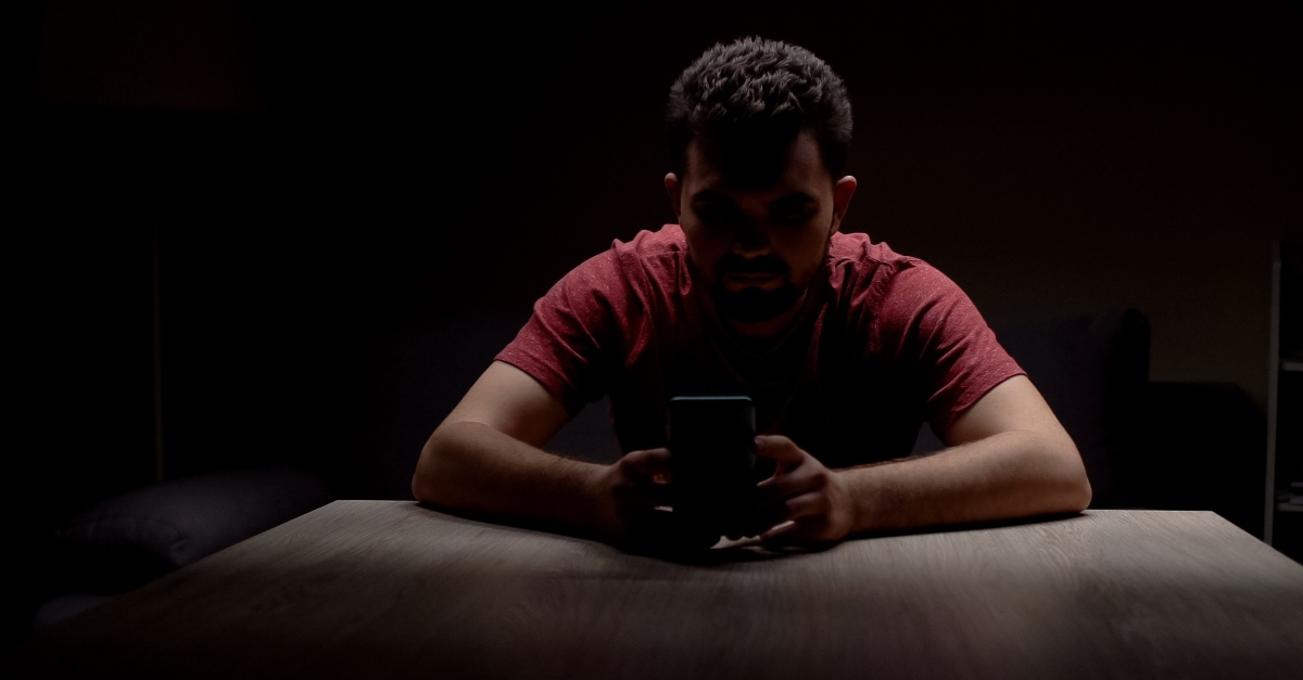 man alone in dark on smartphone God Sees Whats Done in the Dark