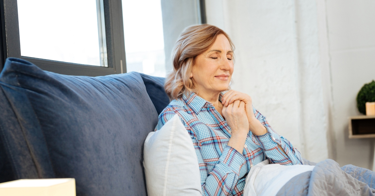 senior woman peacefully praying for an abundant life on her sofa