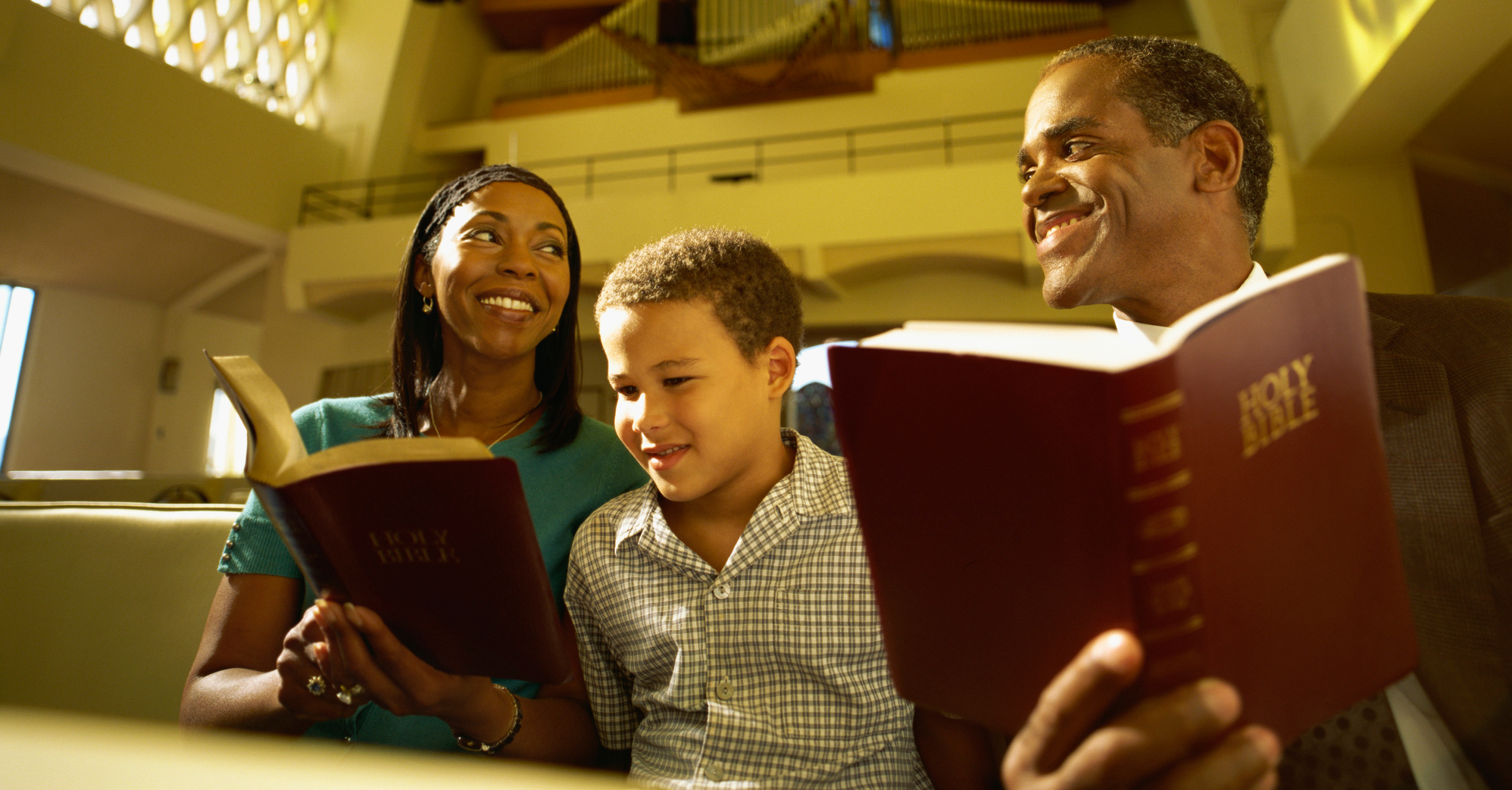 couple reading bible in church with family