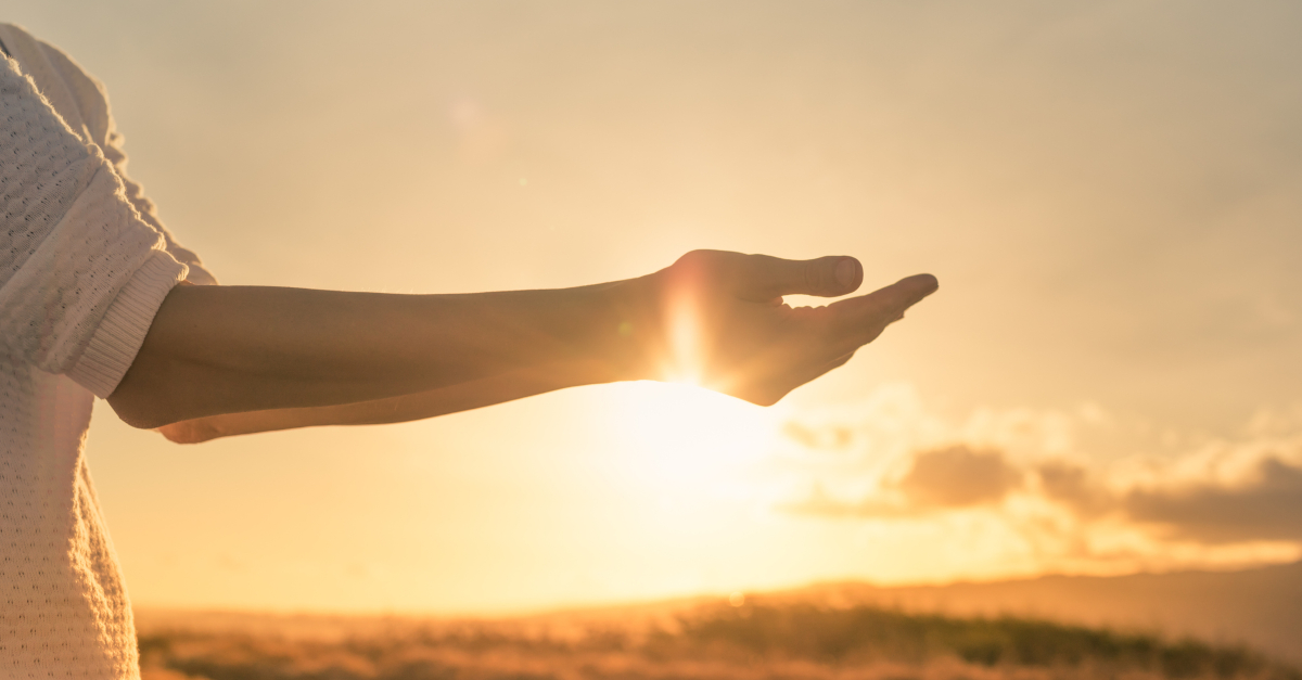 woman arms out at sunrise giving burdens to God