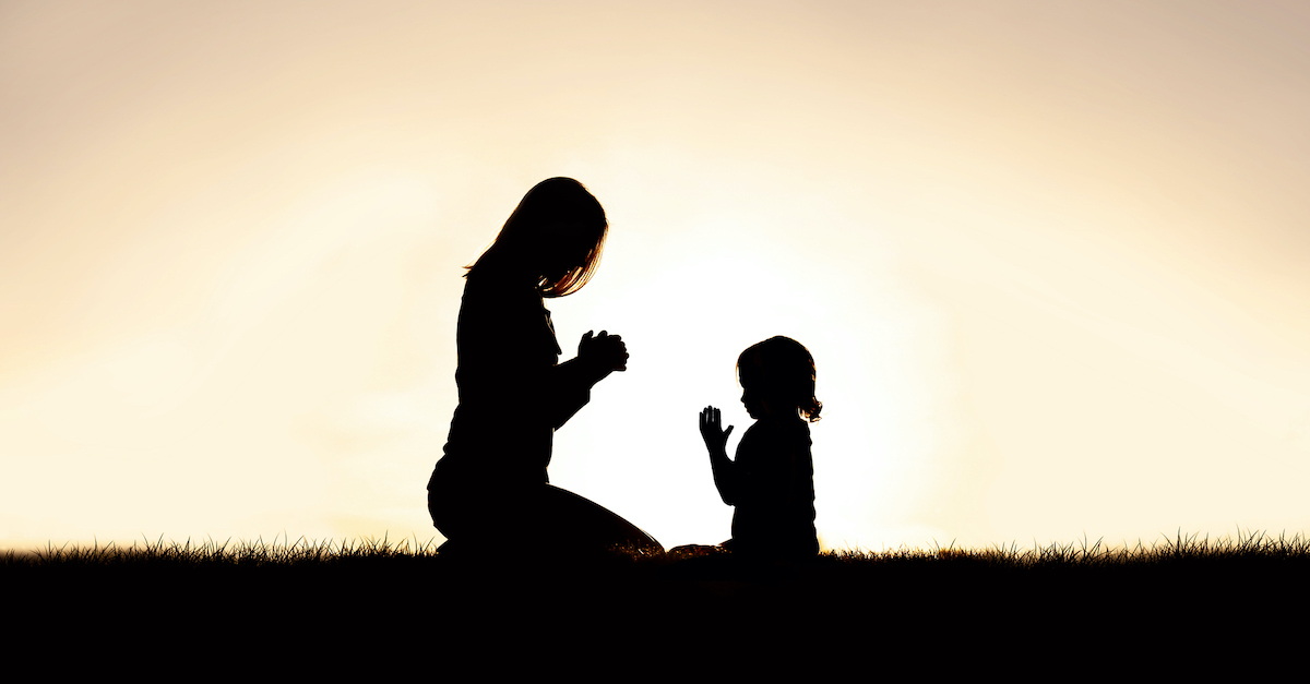 silhouette at sunset of mother and daughter praying outside, generational curses prayer