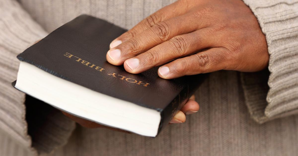 man hands holding open bible