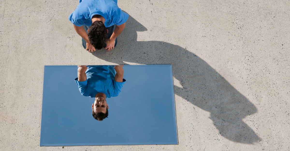 man looking in mirror at reflection on ground