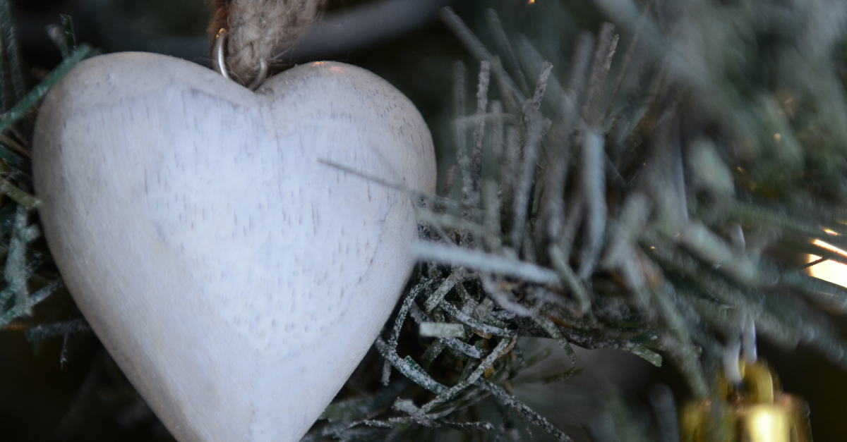closeup of white wooden heart handmade christmas tree ornament