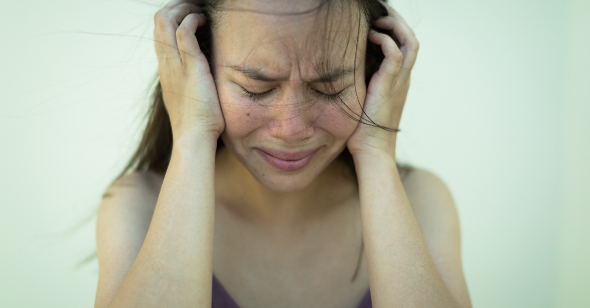woman holding her head looking scared and distressed, how to pray when thoughts out of control