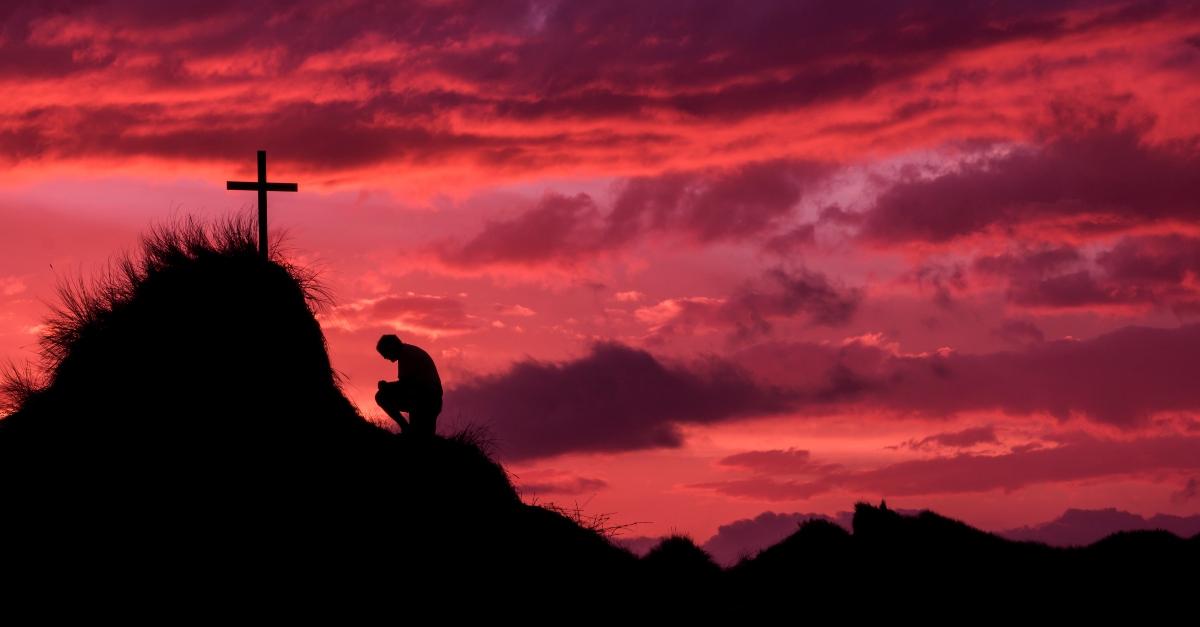 Man kneeling in front of the cross on Golgatha