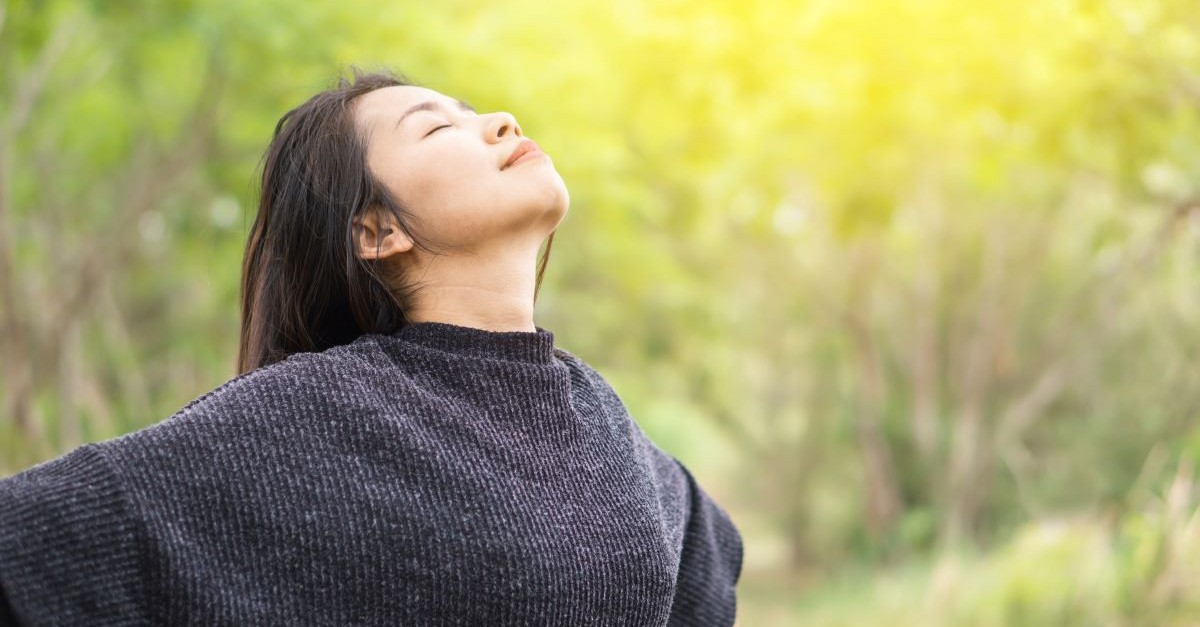 woman eyes closed facing sky, how wonder can help you break free from fear