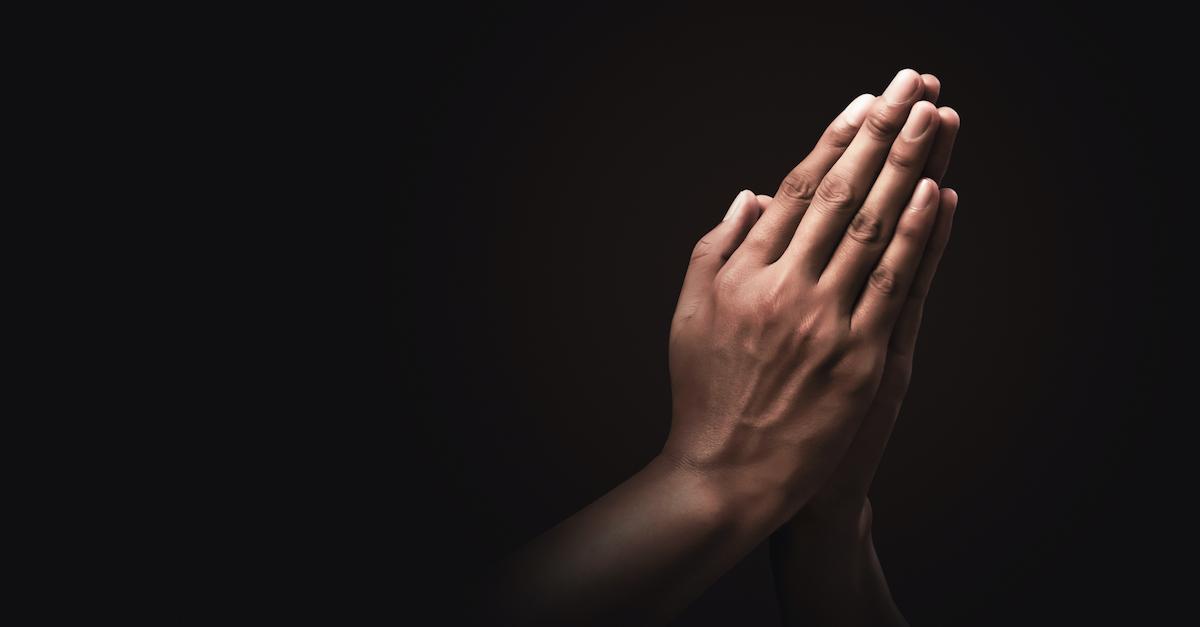 prayer hands against black background