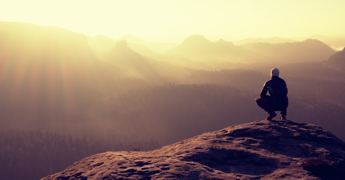 man crouching on mountain top sun setting