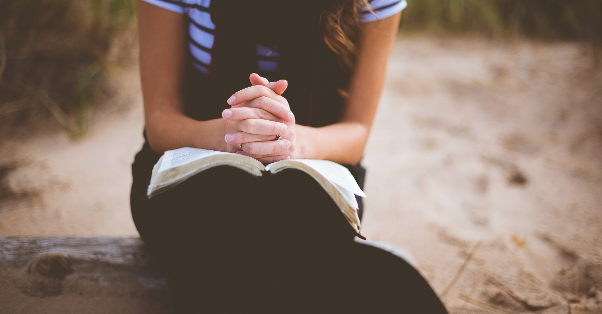 woman praying with bible open outside