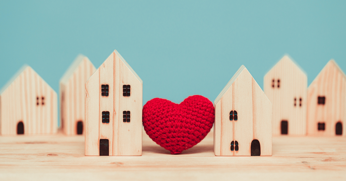 model wooden houses with a red crochet heart in the middle, love is patient love is kind