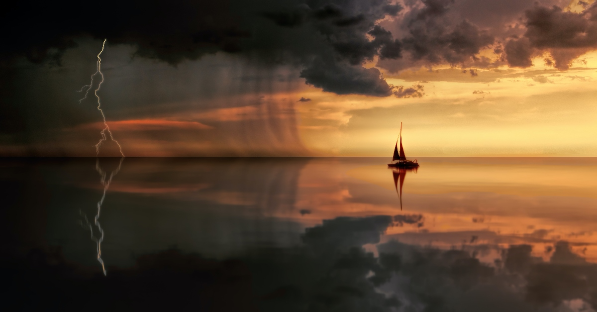 boat sailing into storm clouds over sea