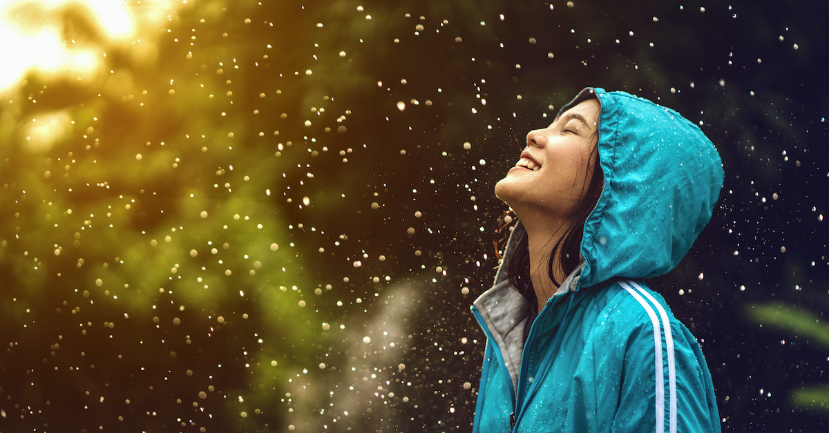 happy woman smiling in the rain with sunshine peaking through clouds, what is joy