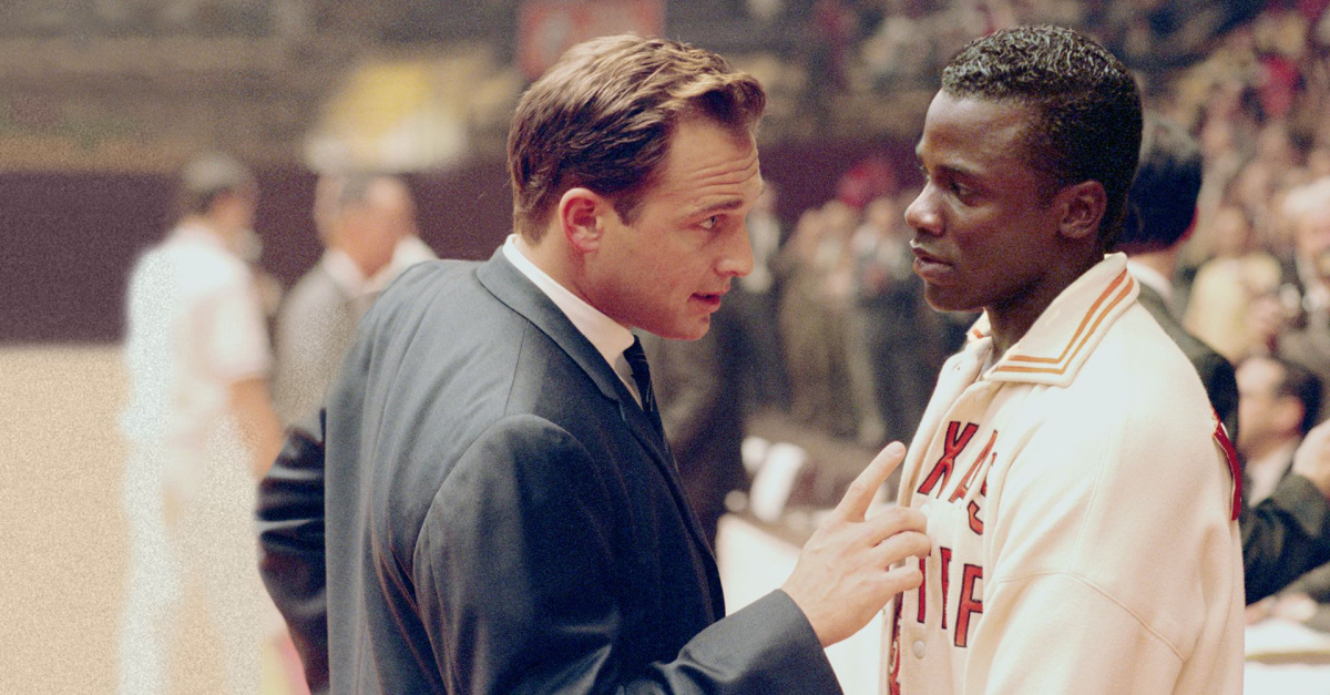 A Basketball coach talking to a player during a game
