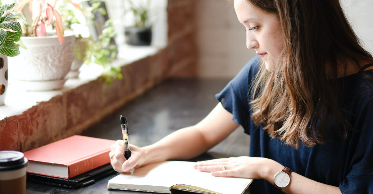 woman journaling in coffee shop