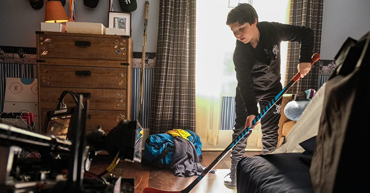 a young boy playing hockey in his room