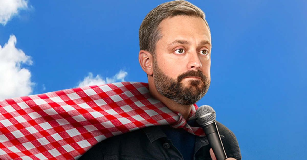 Nate Bargatze wearing a tablecloth cape and holding a microphone
