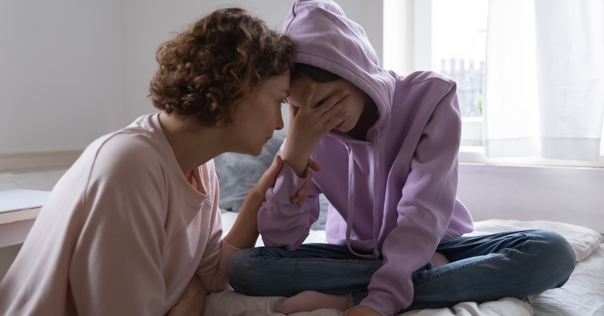 mom sitting with teen daughter who looks worried and depressed