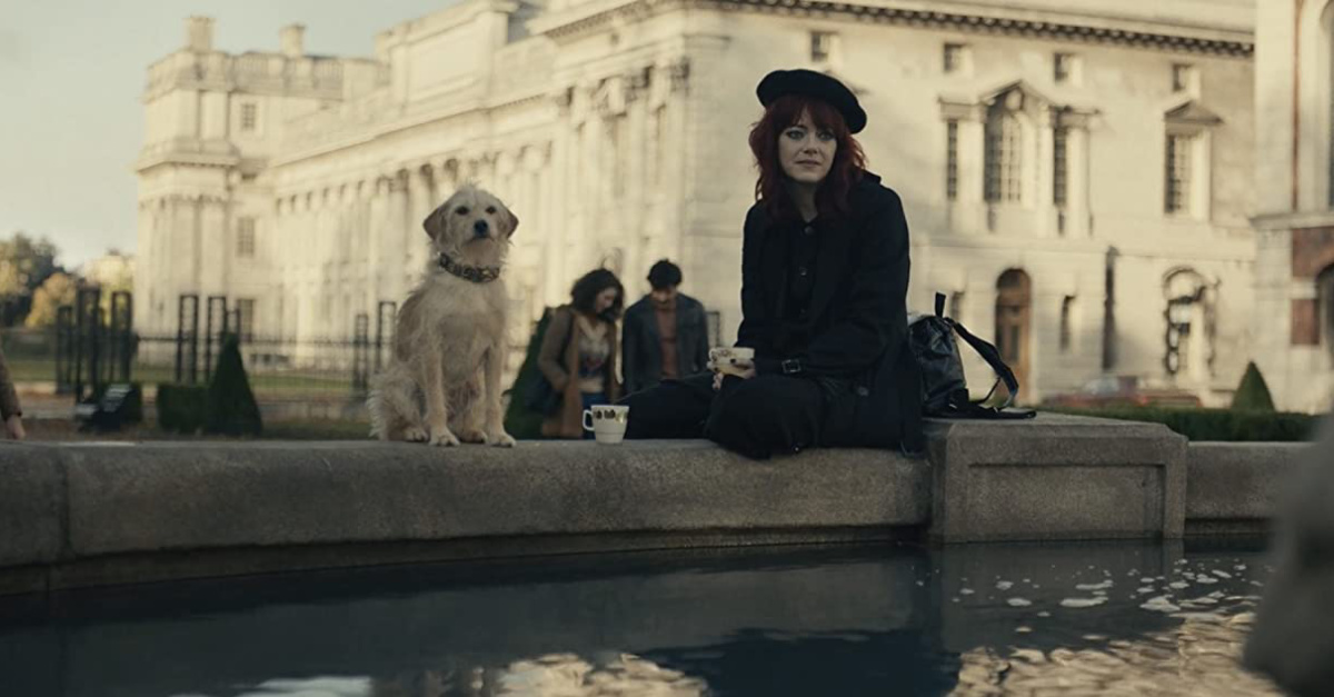 Emma Stone and a dog sitting at a fountain in Cruela