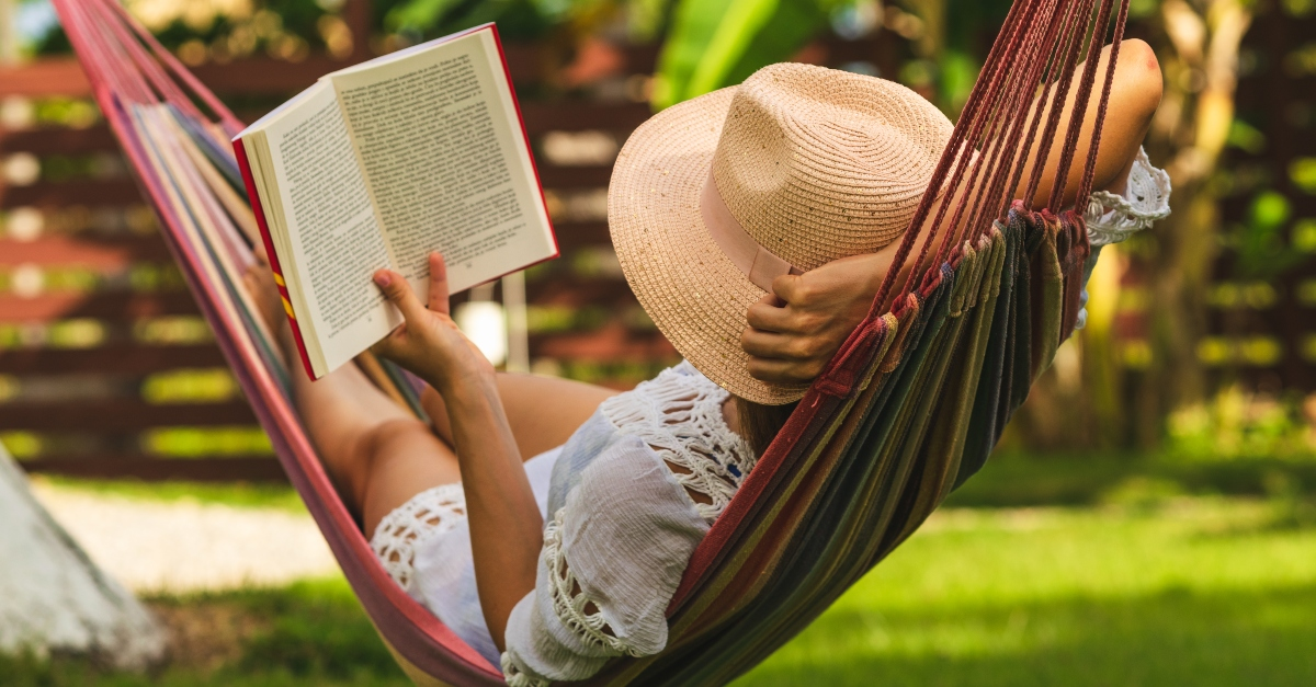 Woman relaxing in a hammock with a book