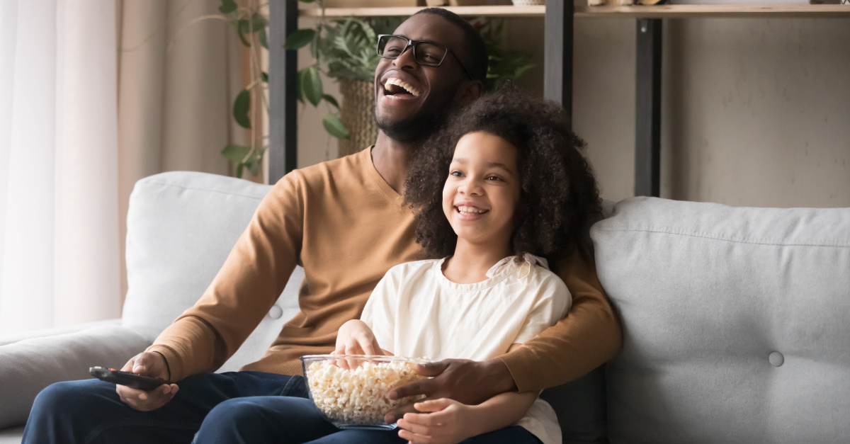 a dad and daughter watching a movie, Inspiring Movies about Dads for Father's Day