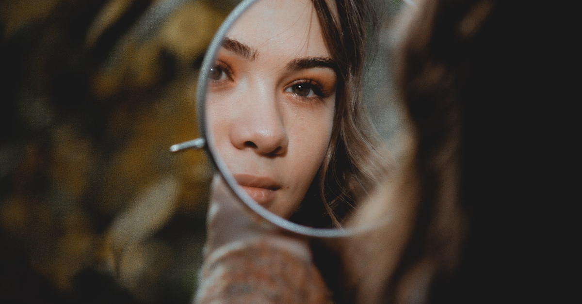 girl looking in small mirror outdoors, truth about who you are