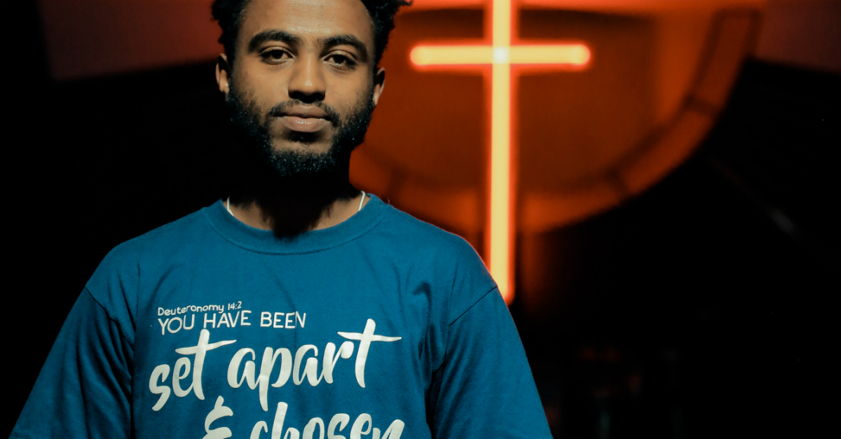 man with set apart tshirt on standing in front of glowing cross