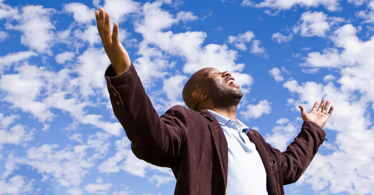man praising arms out and face toward blue sky