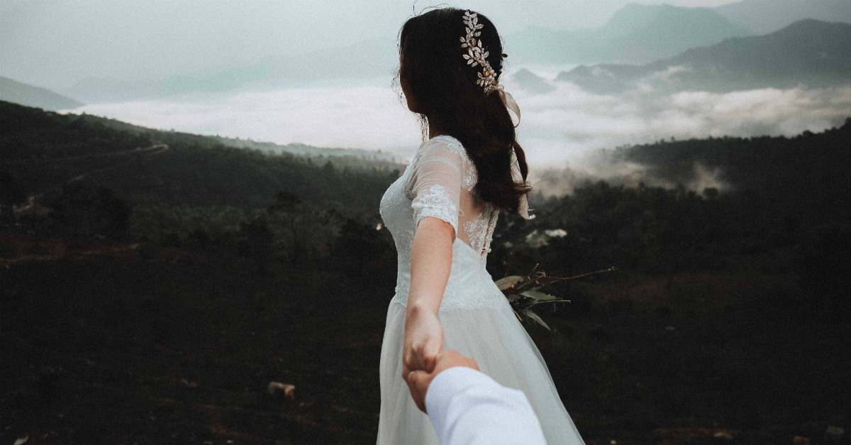 Bride looking out over mountain landscape holding Groom's hand off camera, premarital sex effects