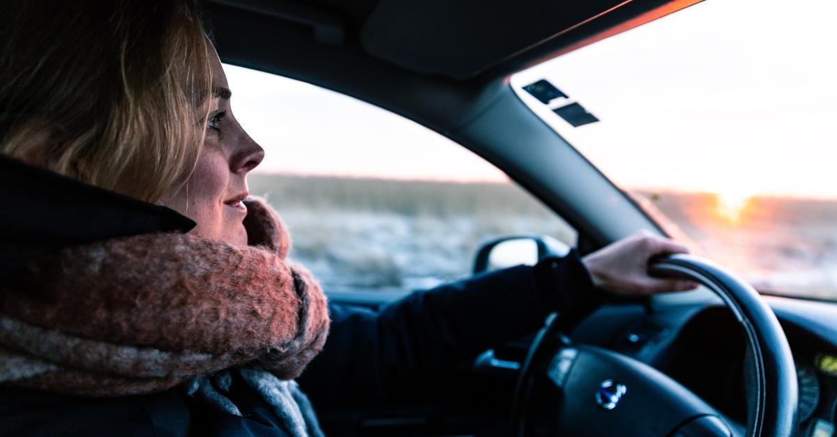 woman driving car praying during commute to work