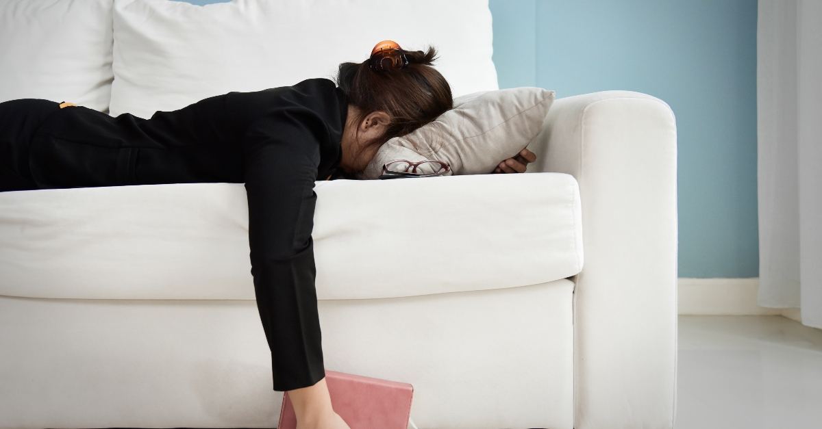 woman exhausted face down on couch