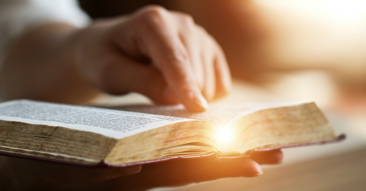 finger pointing to verse in open Bible with light shining on it