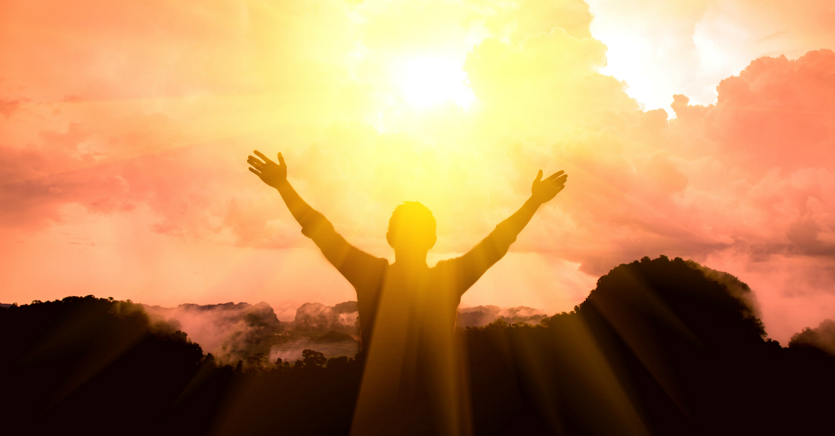 back view of person with arms up and out wide in praise at sunrise